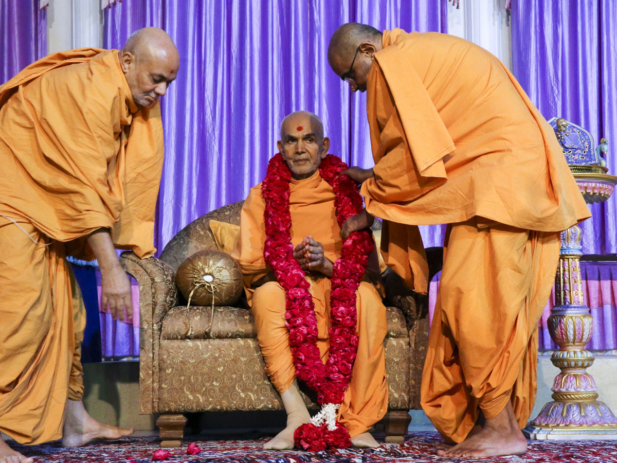 Pujya Viveksagar Swami and Gnaneshwar Swami welcome Swamishri with a garland