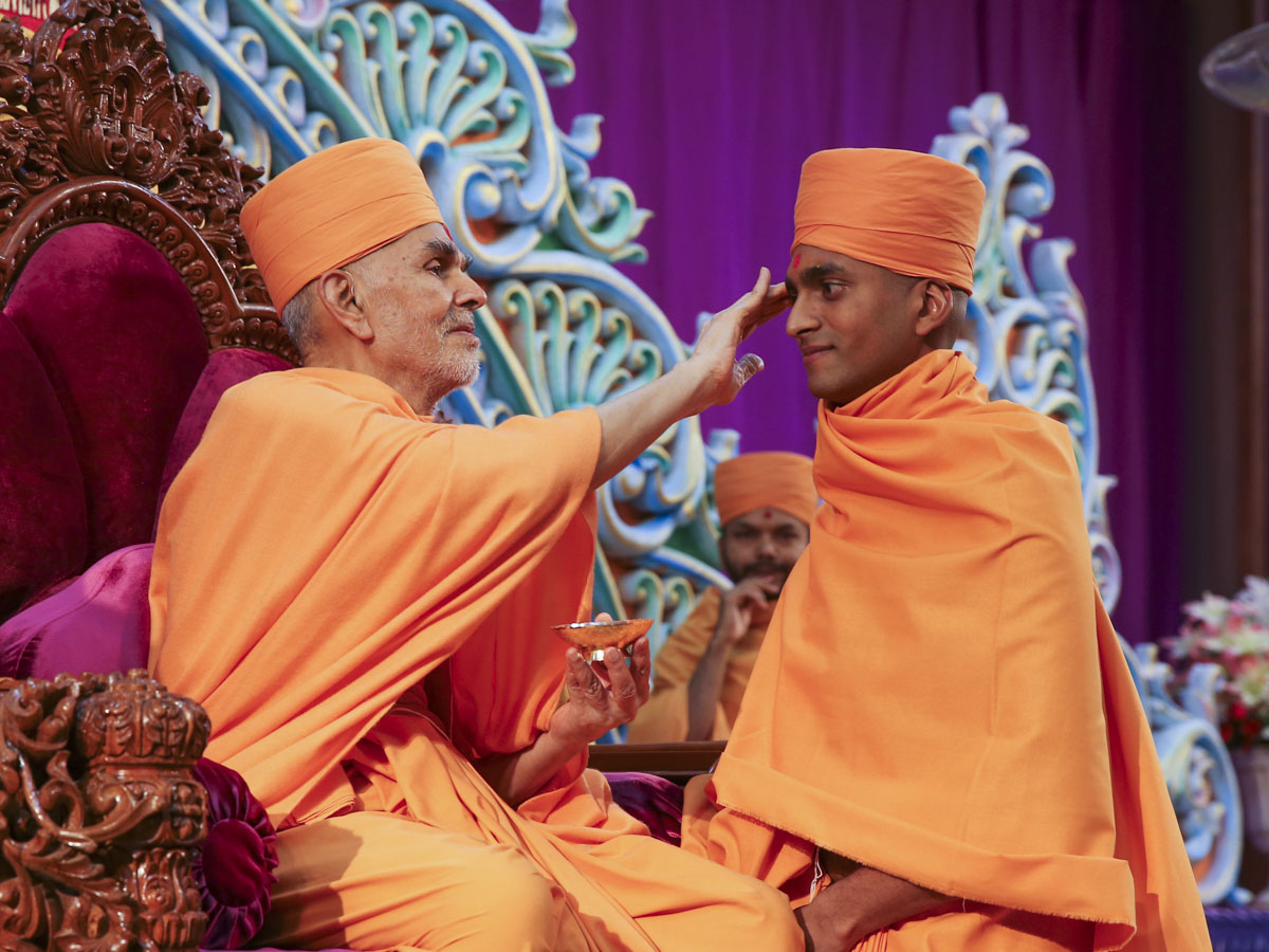 Swamishri gives diksha mantra to newly initiated sadhu and blesses him