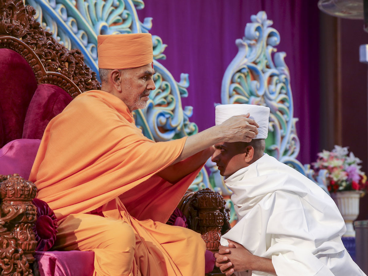 Swamishri gives diksha mantra to newly initiated parshad and blesses him
