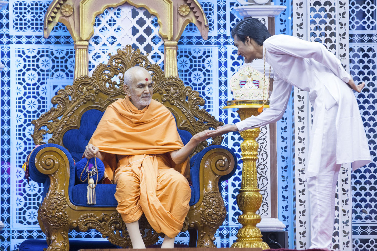 A youth interacts with Swamishri