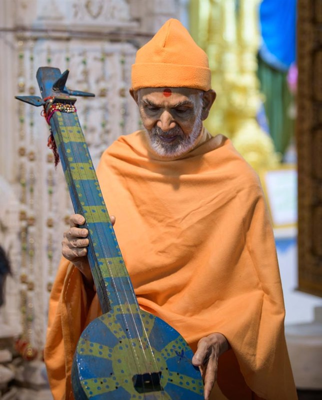Swamishri sanctifies a tribal musical instrument