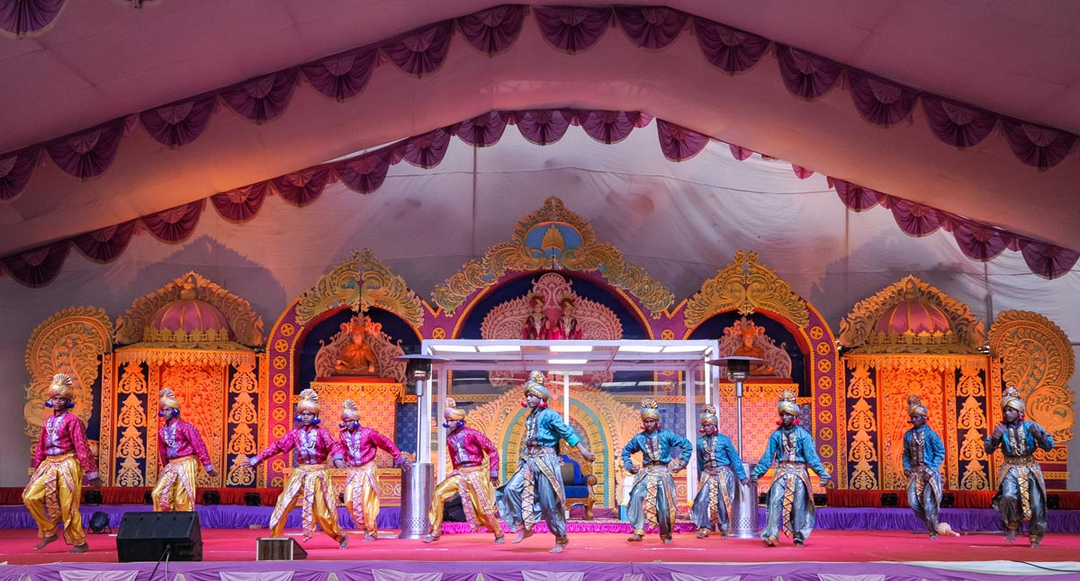 Tribal youths perform a dance in the evening satsang assembly