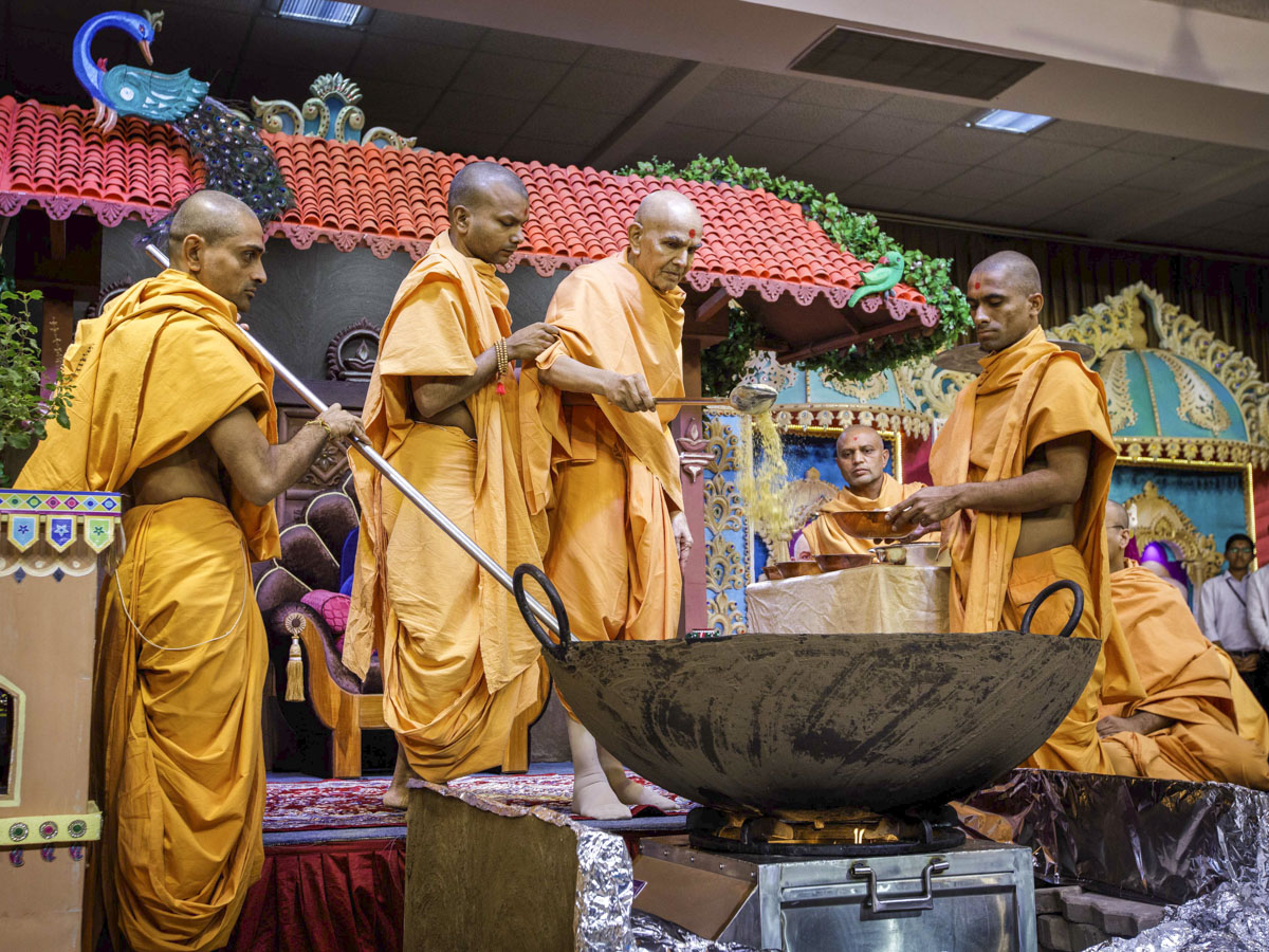 Swamishri adds ingredients to the shak mixture