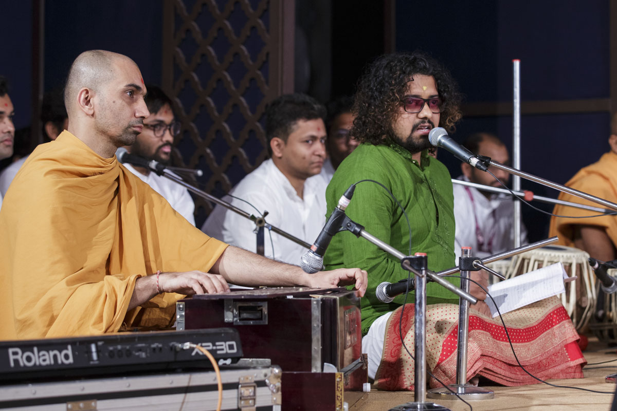 A youth sing kirtans in Swamishri's morning puja