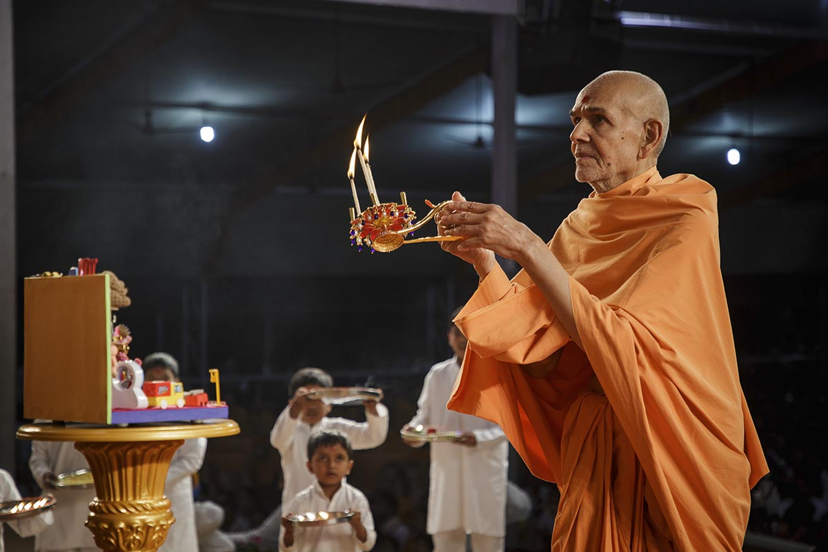 Swamishri performs the evening arti at the beginning of the Bal Din assembly