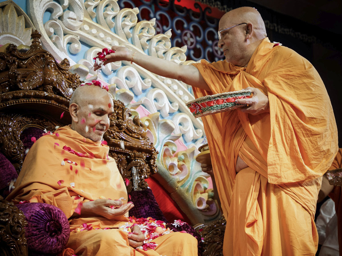 Ghanshyamcharan Swami showers flower petals on Swamishri