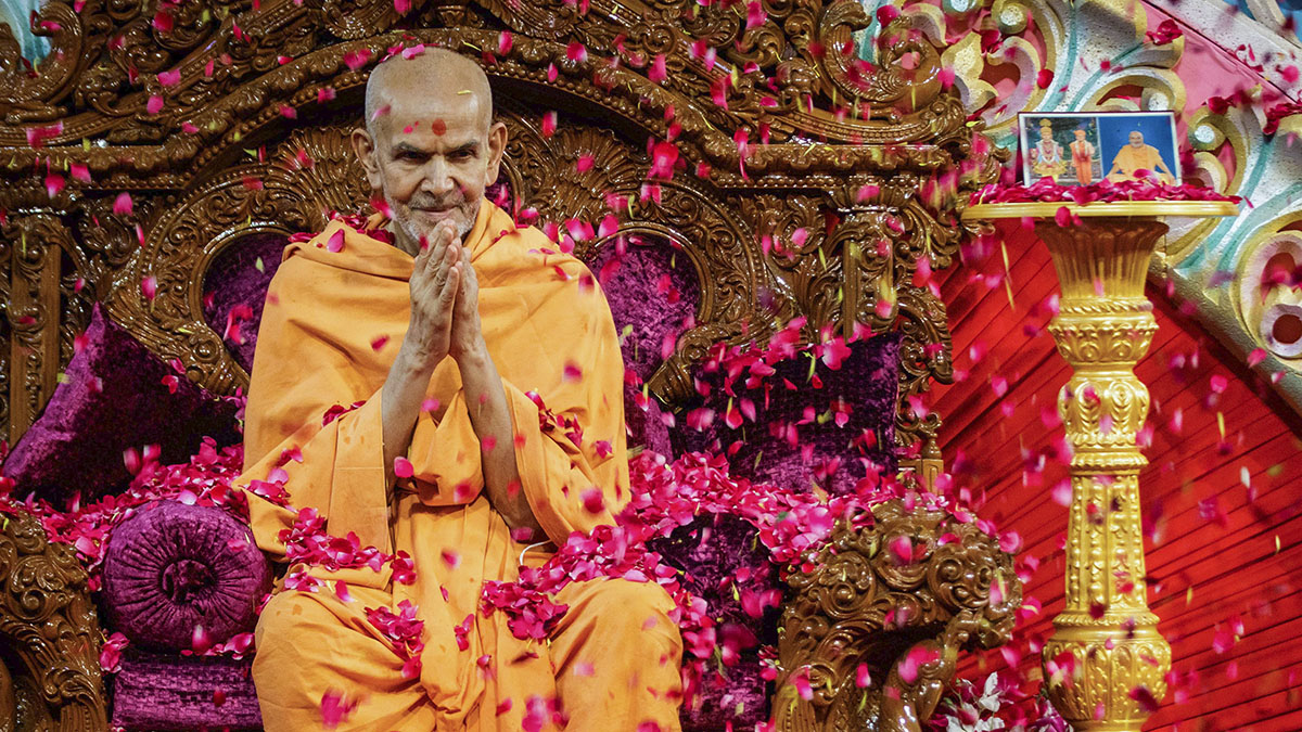 Devotees shower flower petals on Swamishri