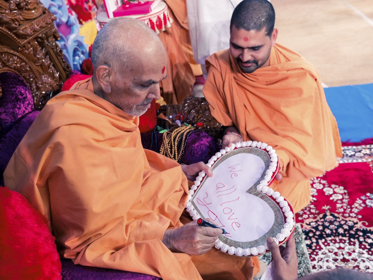 Swamishri writes blessings on a card