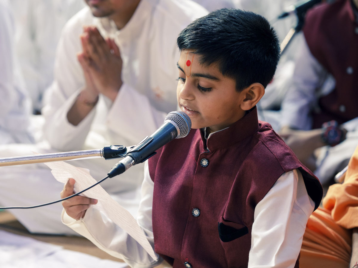 A child sings a kirtan in Swamishri's morning puja