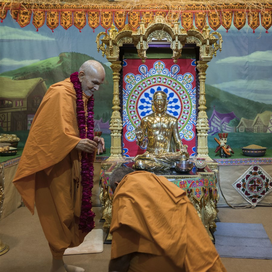 Atmakirti Swami welcomes Swamishri with a garland