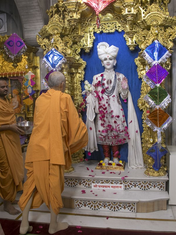 Swamishri showers flower petals on Shri Ghanshyam Maharaj
