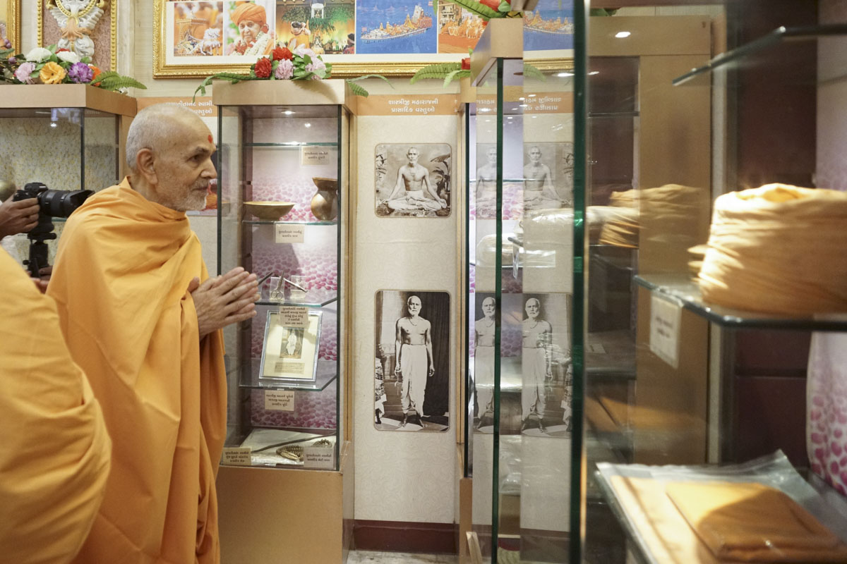 Swamishri engrossed in darshan of holy relics of Bhagwan Swaminarayan and Shri Guru Parampara