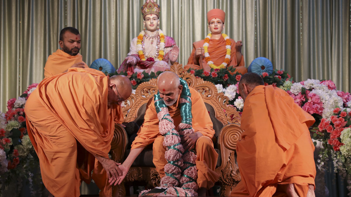 Pujya Ishwarcharan Swami and Anandswarup Swami honor Swamishri with a garland