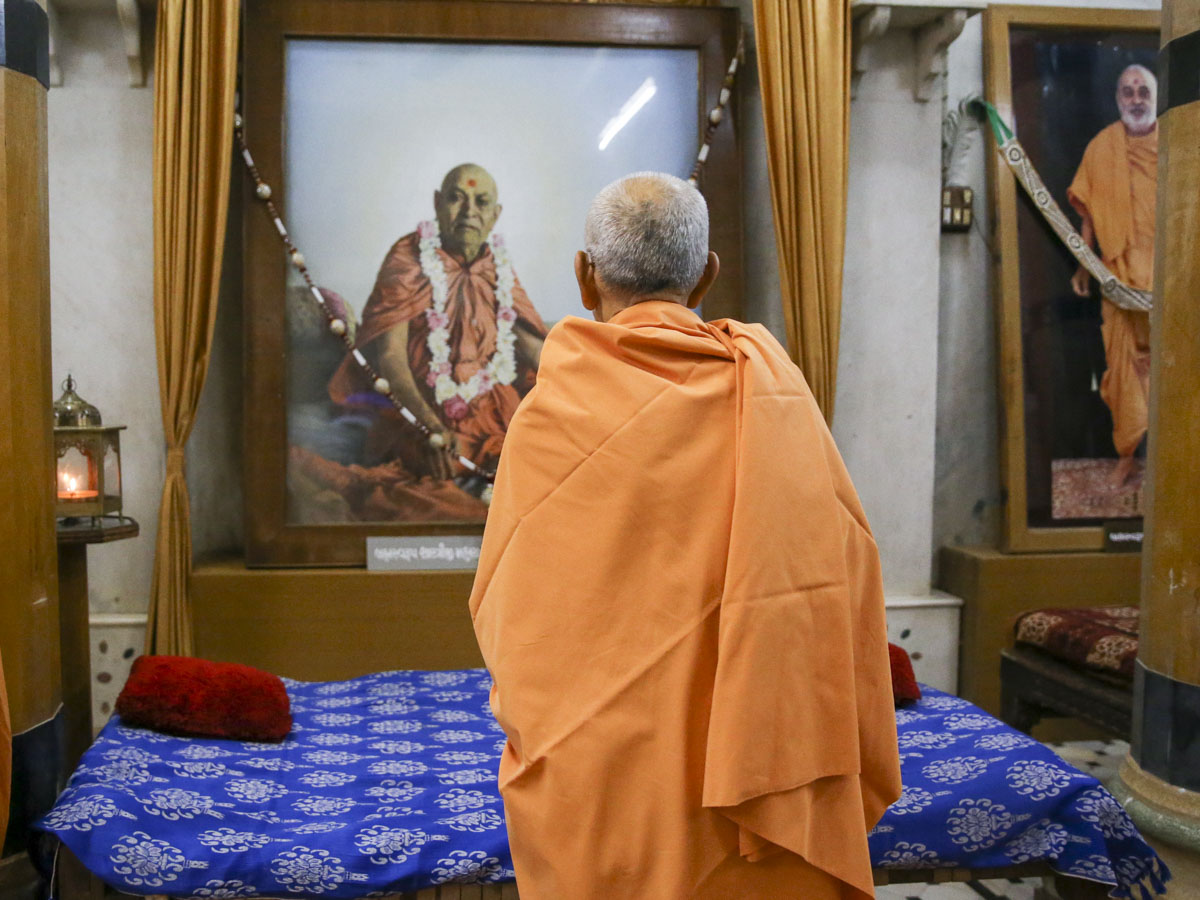 Swamishri engrossed in darshan of Brahmaswarup Shastriji Maharaj in the Rangmandap