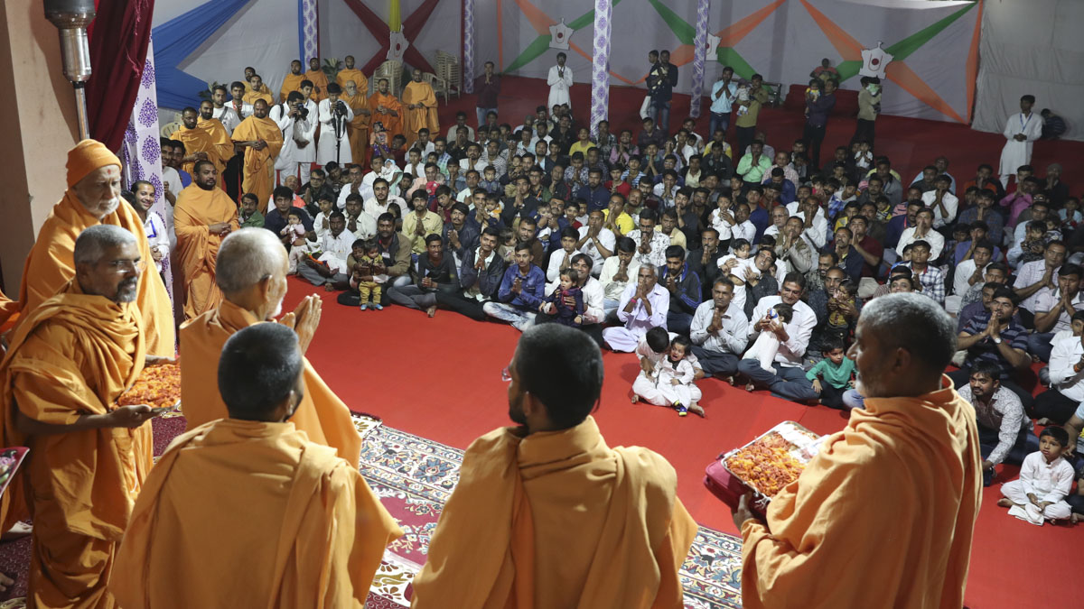 Parents and their young children doing darshan of Swamishri
