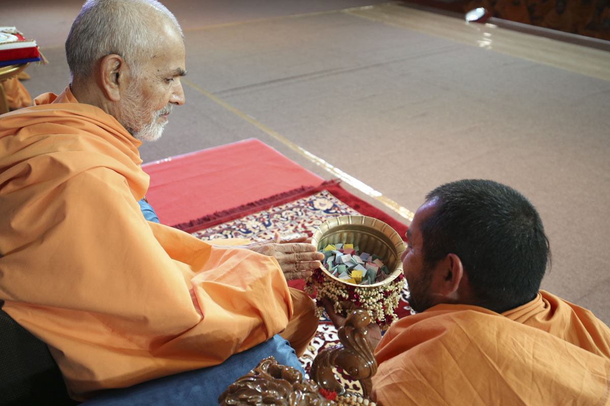 Swamishri sanctifies a kalash with prayers from the students