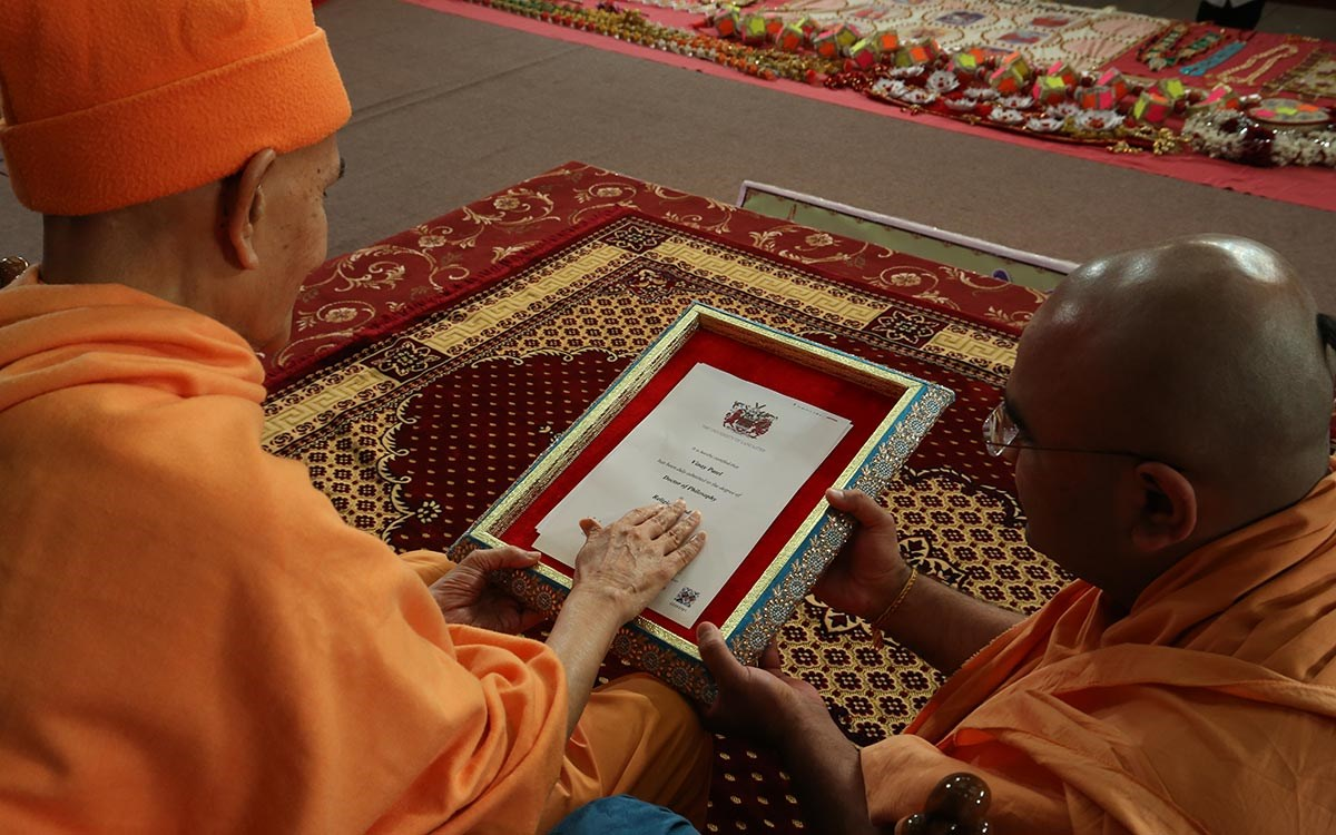 Swamishri sanctifies the Ph.D. certificates awarded to Aksharanand Swami by University of Lancaster