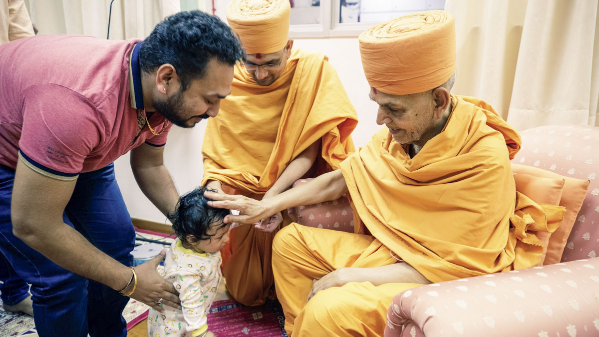 Swamishri blesses a child, 4 Feb 2018