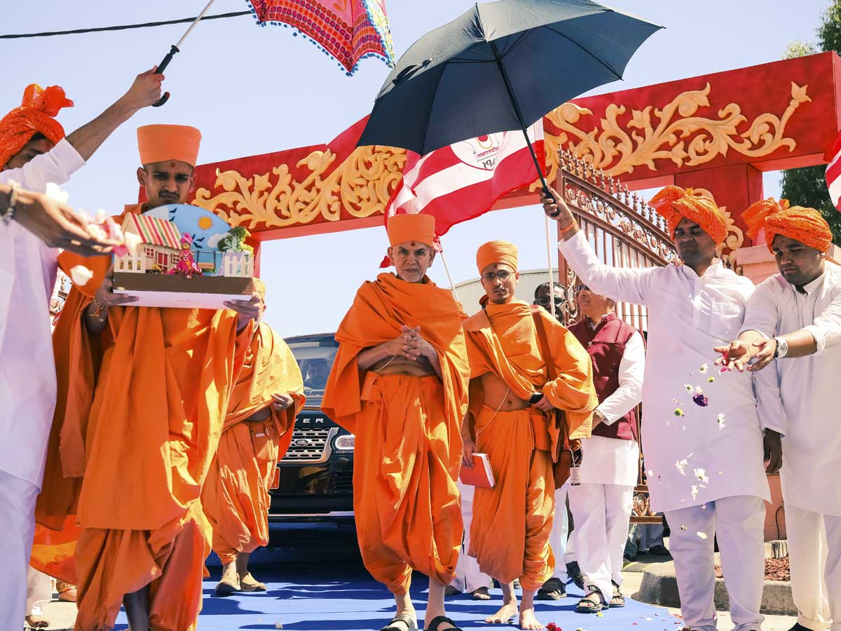 Devotees welcome Swamishri with flower petals
