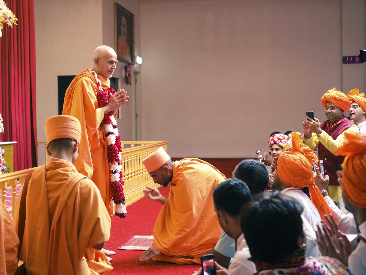 Paramchintan Swami honors Swamishri with a garland