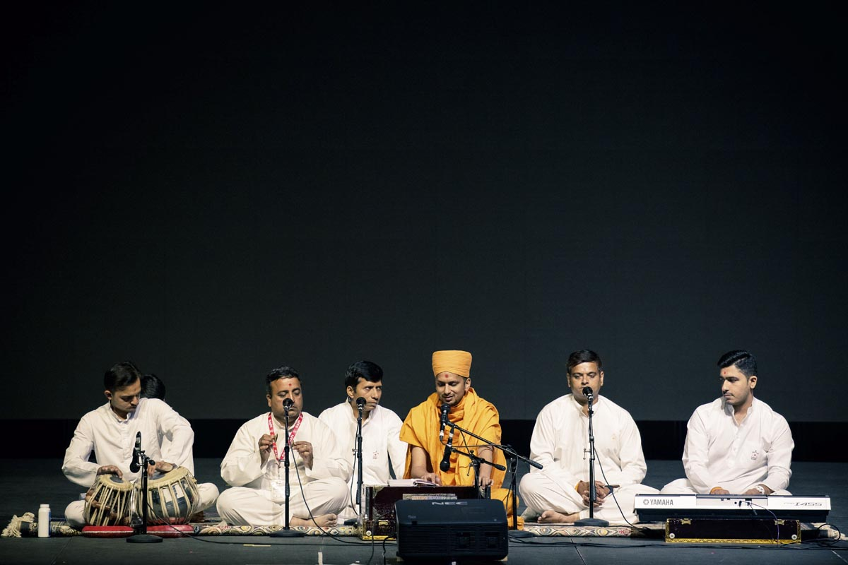A sadhu and youths sing kirtans in the evening cultural program assembly