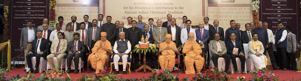 HE Vajubhai Vala, Pujya Ishwarcharan Swami, Pujya Viveksagar Swami and Bhadresh Swami together with university vice-chancellors and representatives