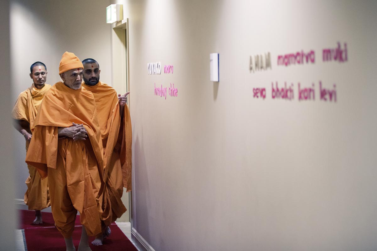 Swamishri reads the devotional message on a wall