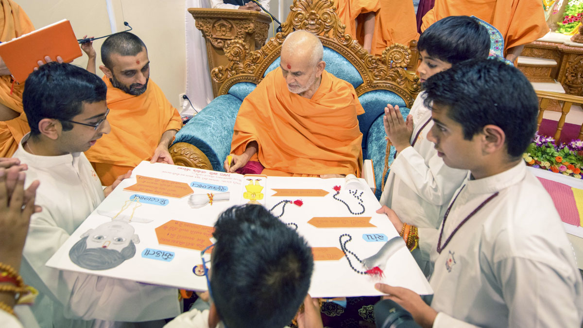 Swamishri observes a card prepared by children