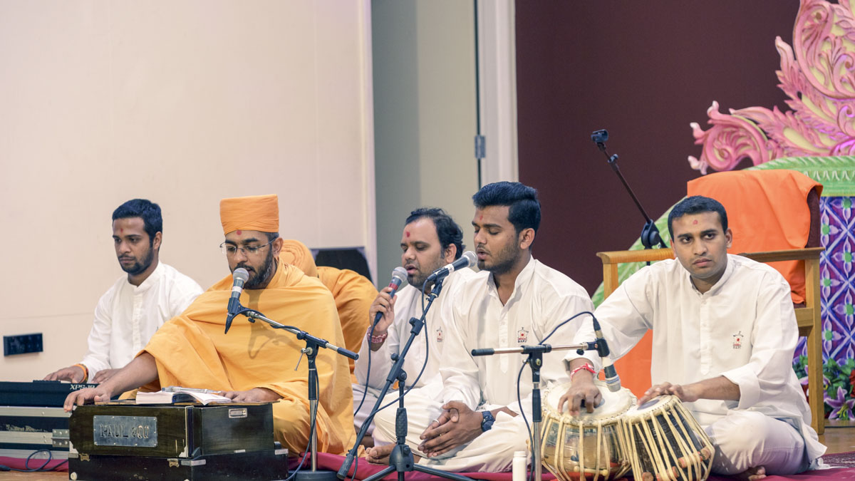 A sadhu and youths sing kirtans in the evening satsang assembly