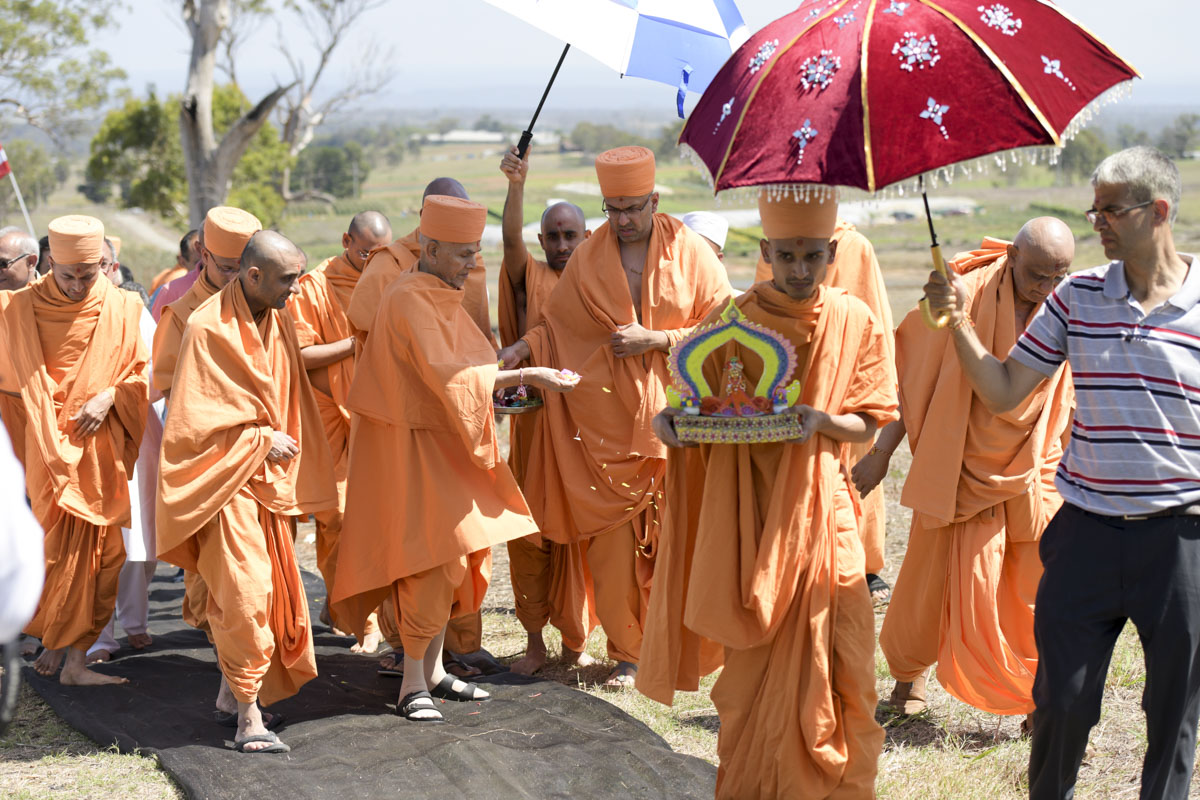 Swamishri showers sanctified flower petals on the site