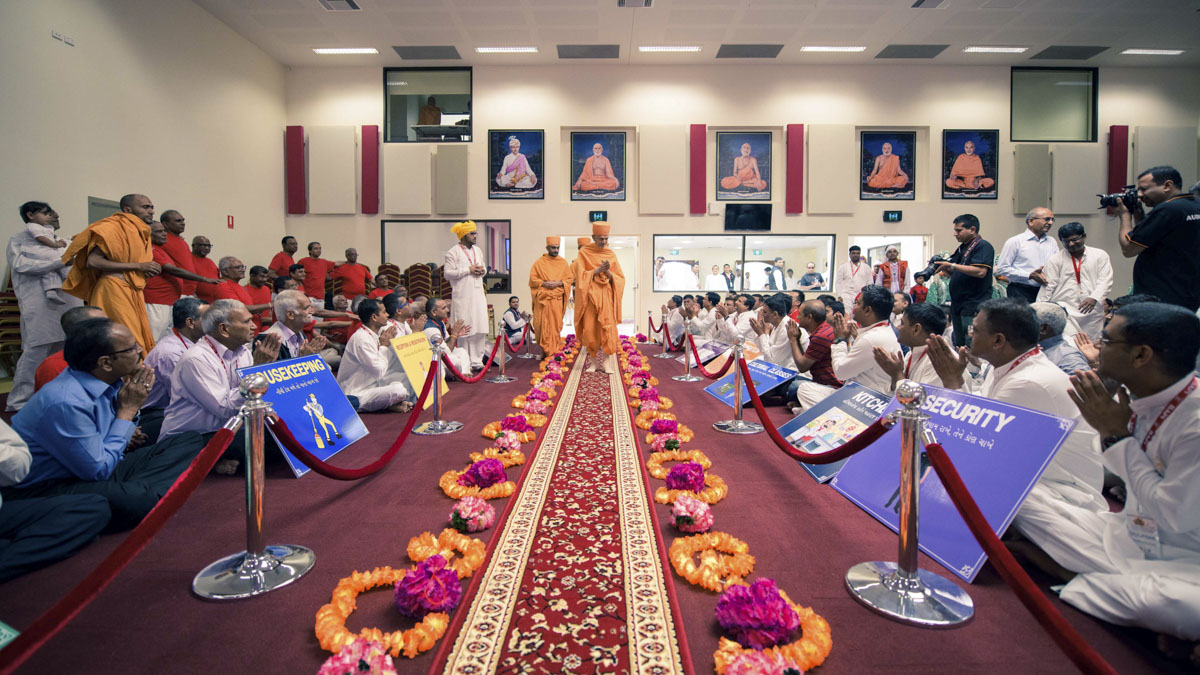 Devotees welcome Swamishri in the mandir hall