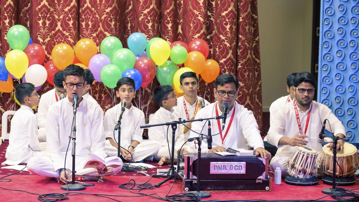 Youths sing kirtans in the assembly
