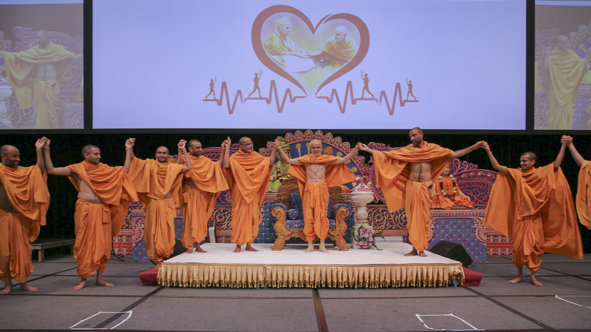 Swamishri joins hands with sadhus and devotees in a gesture of unity