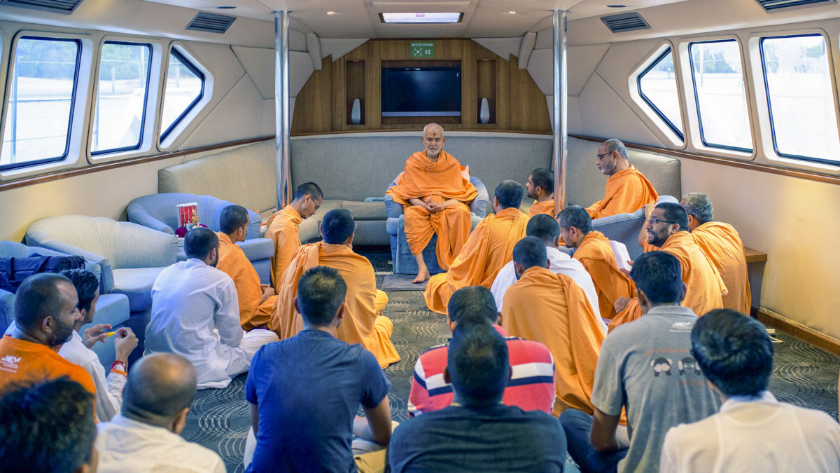 Swamishri on the boat with sadhus and devotees
