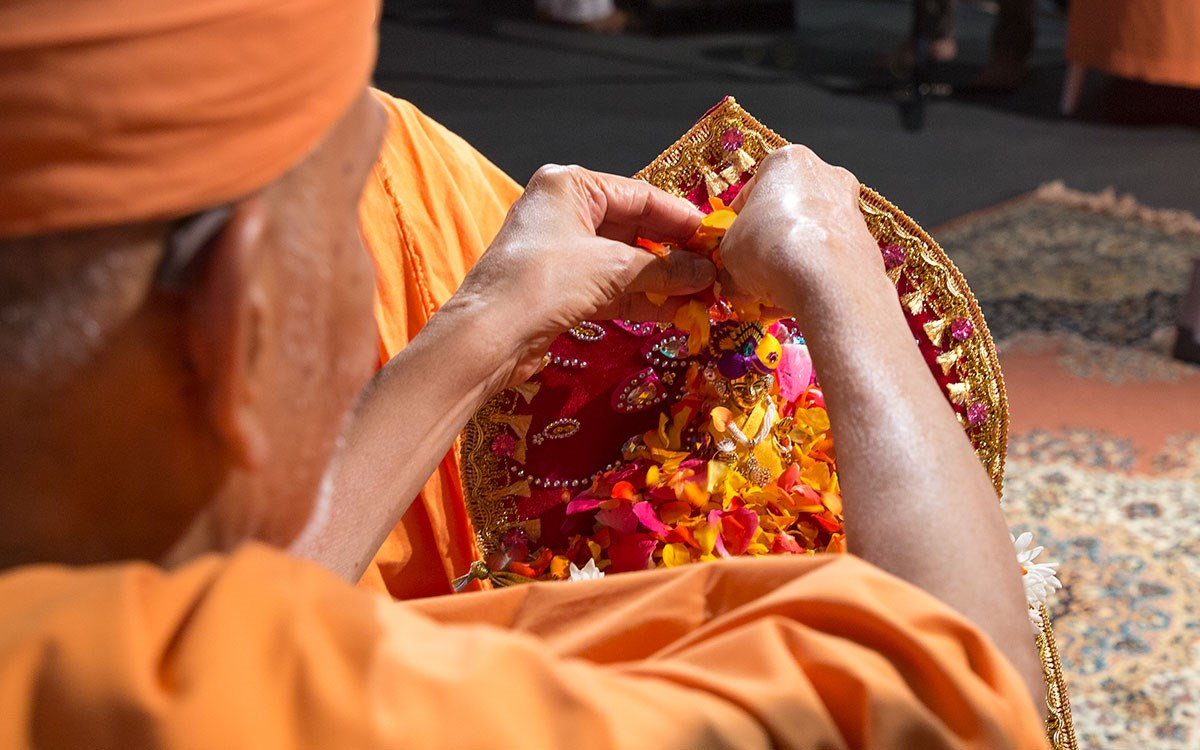 Swamishri showers flower petals on Shri Harikrishna Maharaj