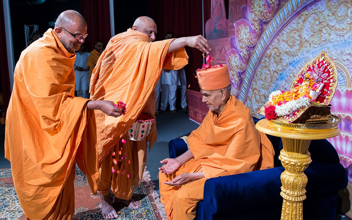 Atmaswarup Swami showers flower petals on Swamishri