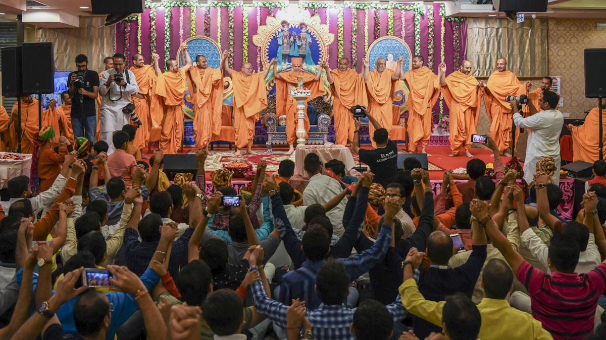 Swamishri joins hands with swamis and devotees in a gesture of unity