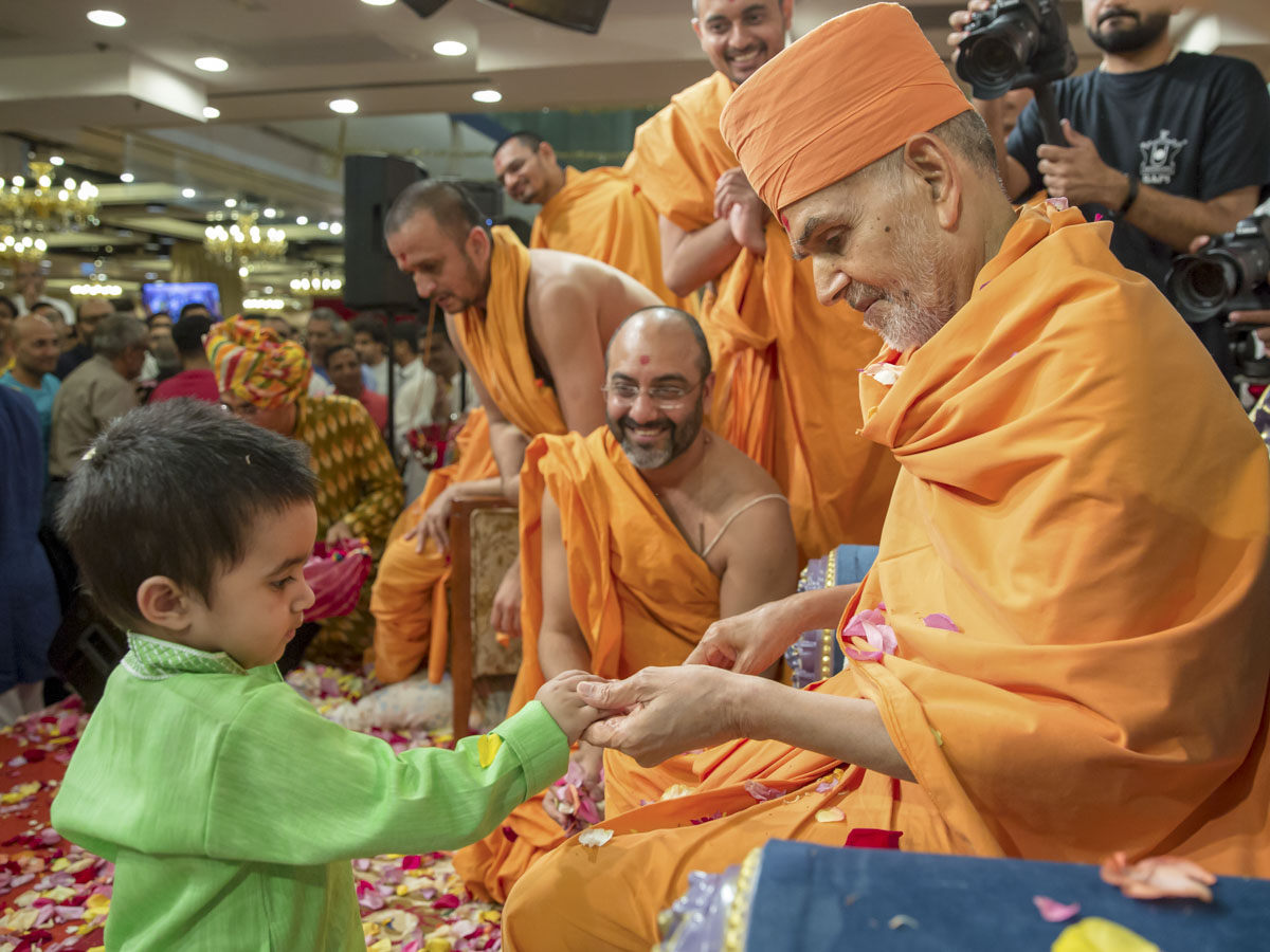 Swamishri interacts with a child