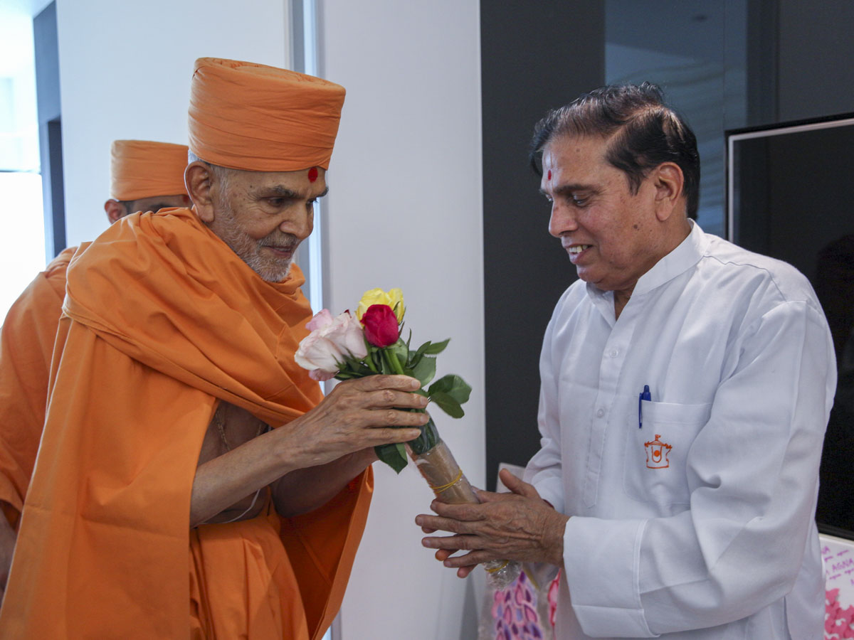 Rajababu Gupta presents flowers to Swamishri