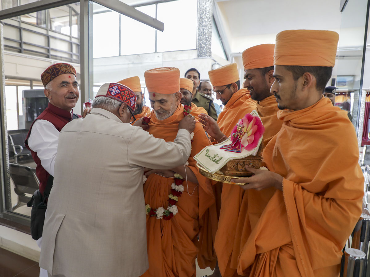 Devotees welcome Swamishri with a garland