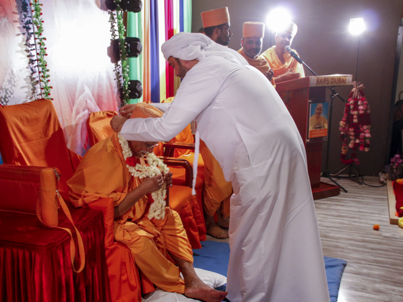 A guest honors Pujya Doctor Swami with a garland