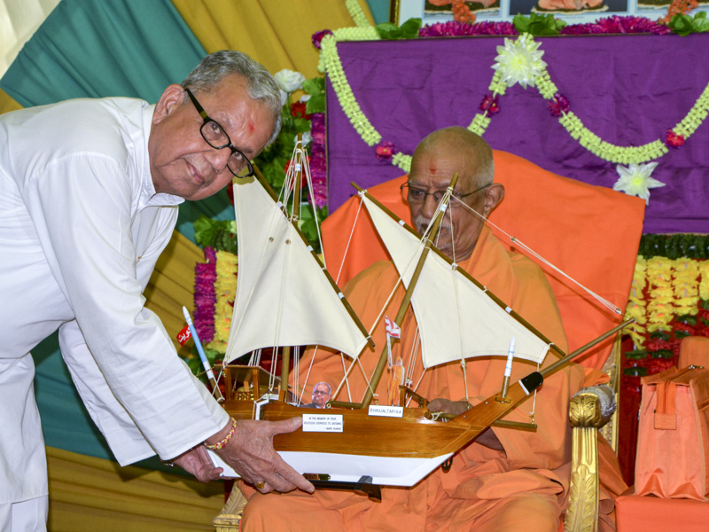 A devotee presents a memento to Pujya Doctor Swami