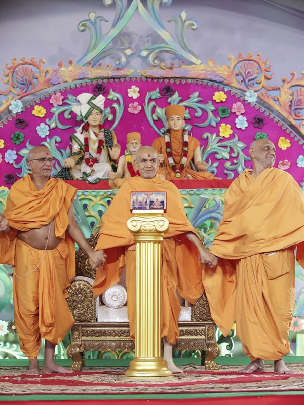 Swamishri joins hands with sadhus in a gesture of unity