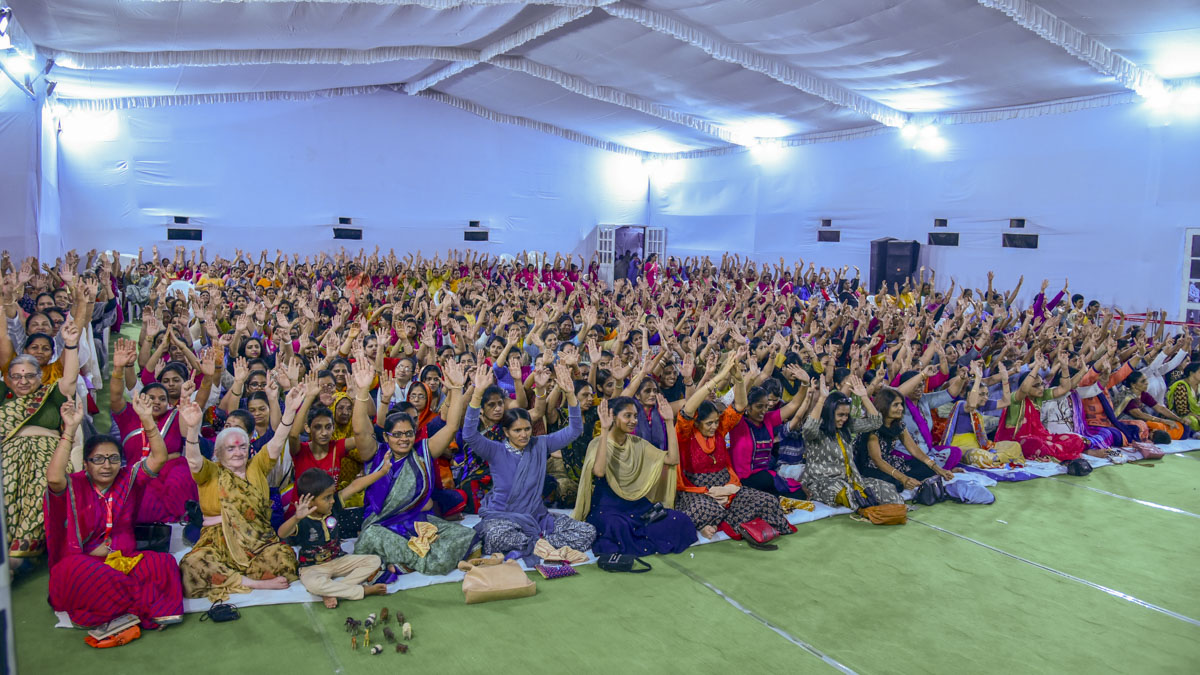 Devotees raise hands in a gesture of unity