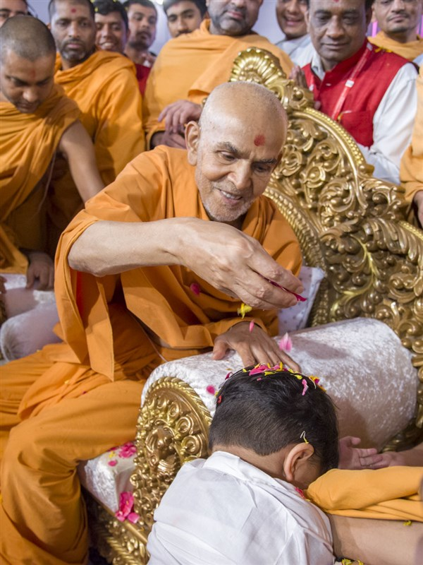 Swamishri showers flower petals on a child