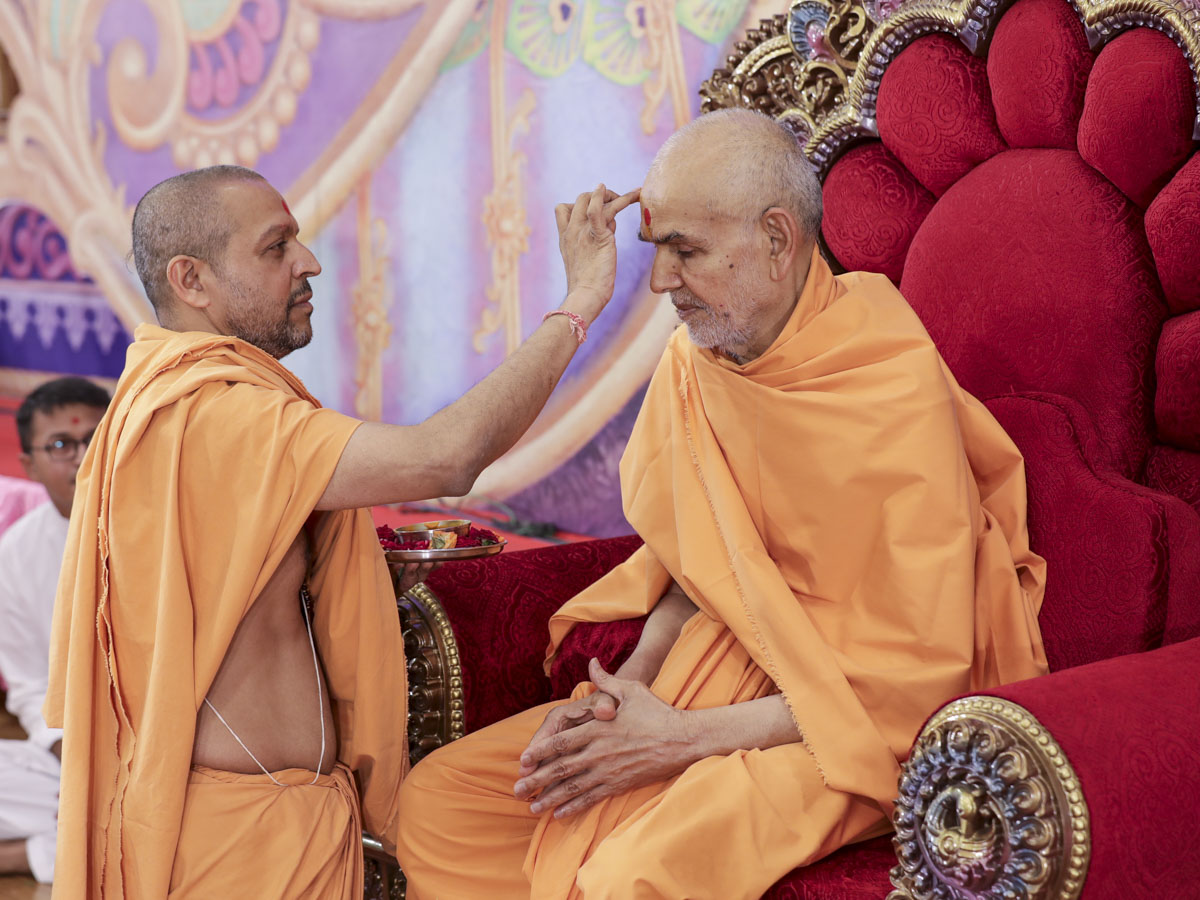 Saraljivan Swami applies chandan to Swamishri