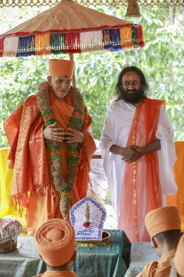 Sri Sri Ravi Shankar honors Swamishri with a garland
