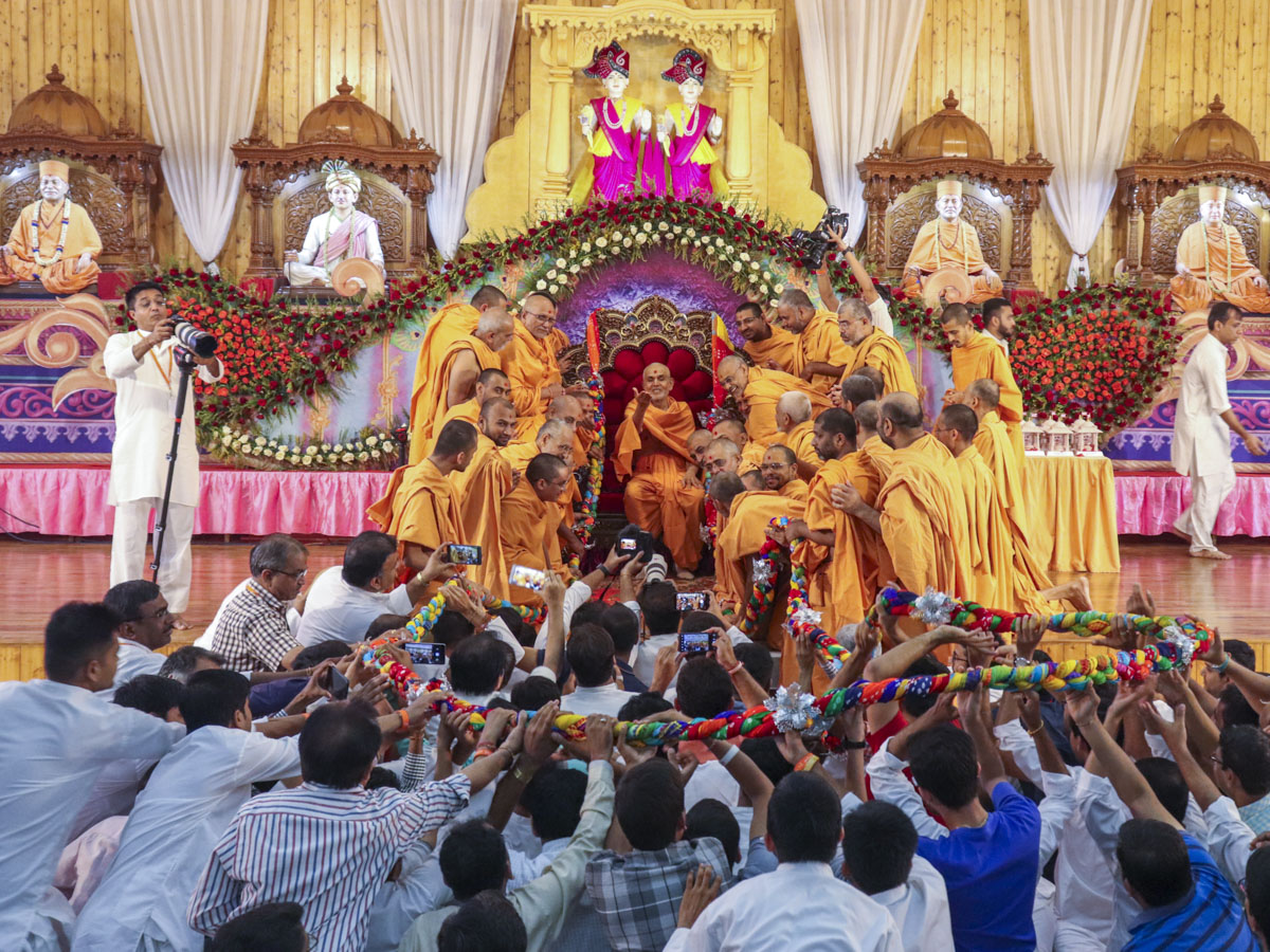 Sadhus and devotees honor Swamishri with a garland