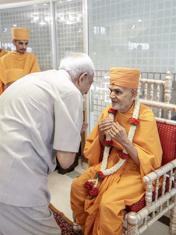 A trustee of the Jalaram mandir honors Swamishri with a garland