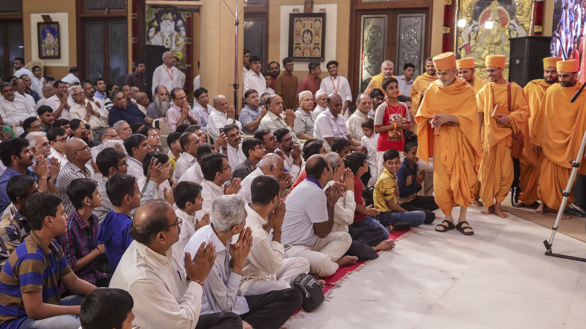 Swamishri greets devotees on arriving in the evening satsang assembly